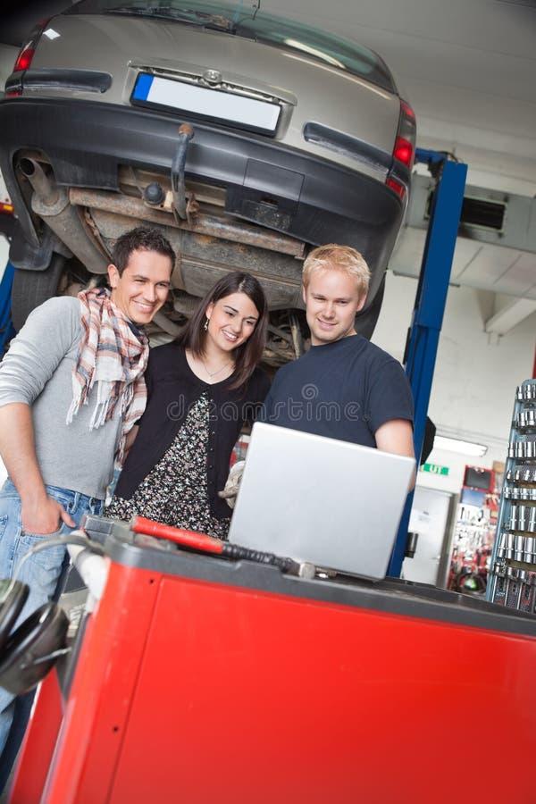 Couples restant avec le mécanicien à l'aide de l'ordinateur portatif photographie stock