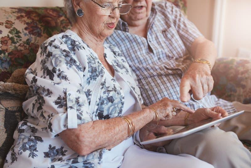 Couples retirés à la maison utilisant l'ordinateur d'écran tactile images libres de droits