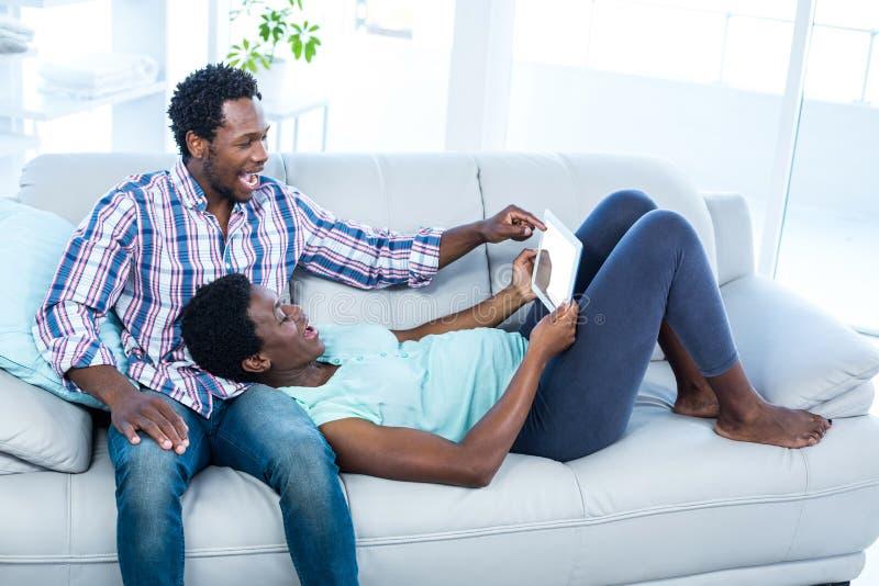 Couples riant et regardant le comprimé photographie stock libre de droits
