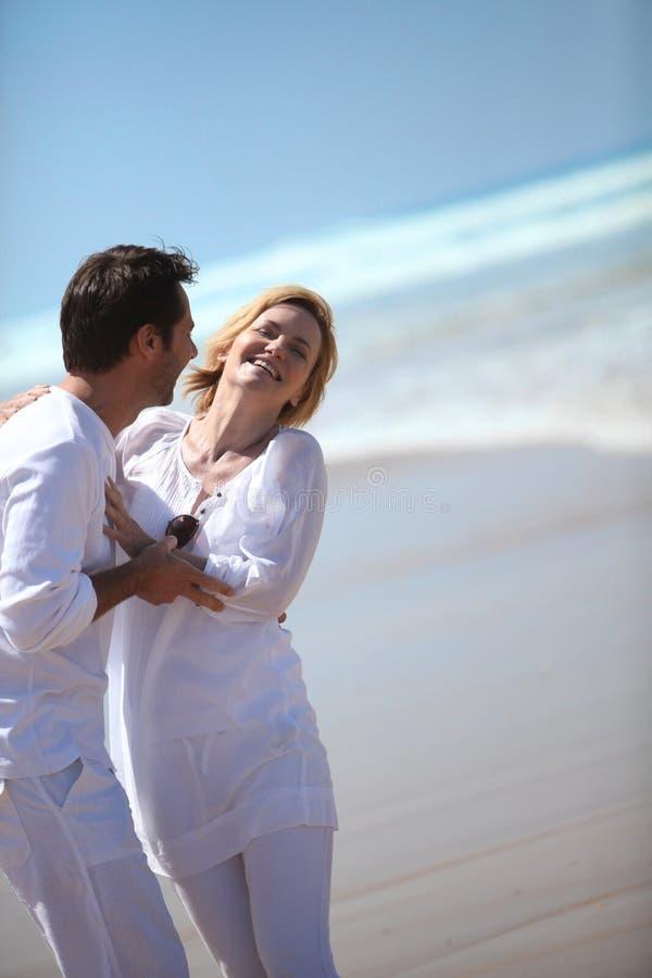 Couples riant par la mer image libre de droits