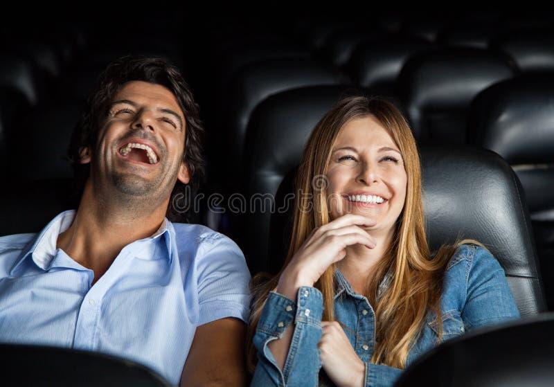 Couples riant tout en observant le film dans le théâtre photo stock