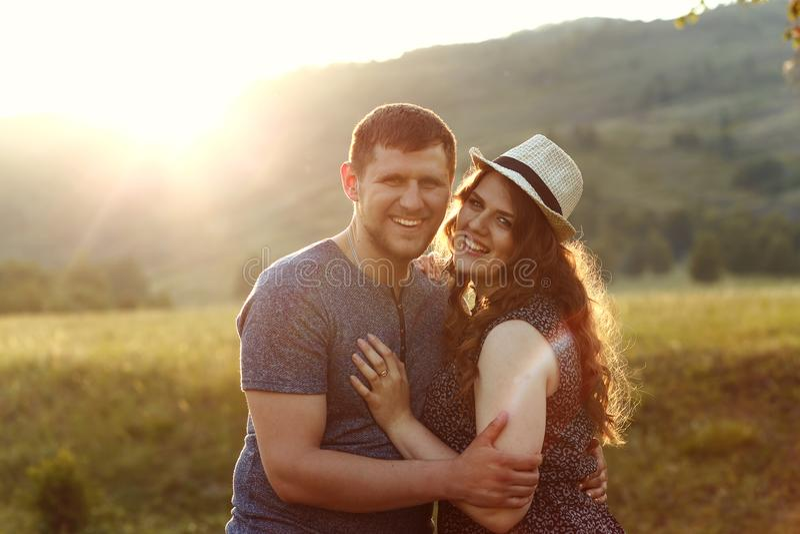 Couples riants dans l'amour au coucher du soleil en nature, lune de miel, montagnes, lumière arrière, lumière molle, émotions, ri photographie stock