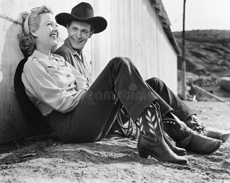 Couples riants dans le vêtement occidental se reposant au sol (toutes les personnes représentées ne sont pas plus long vivantes e image stock