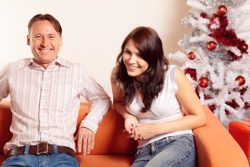 Couples riants de Noël se reposant sur un divan photographie stock libre de droits