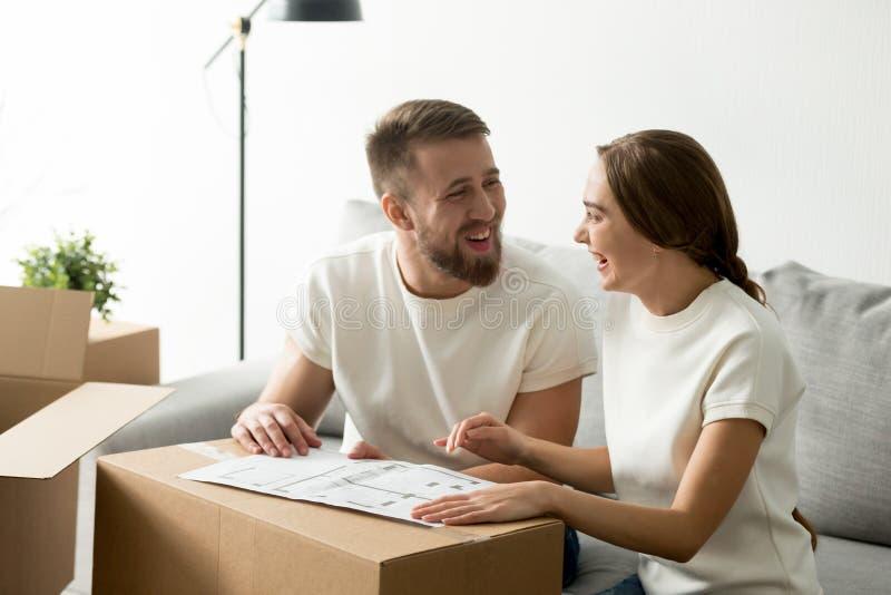 Couples riants heureux discutant le plan architectural de maison photographie stock