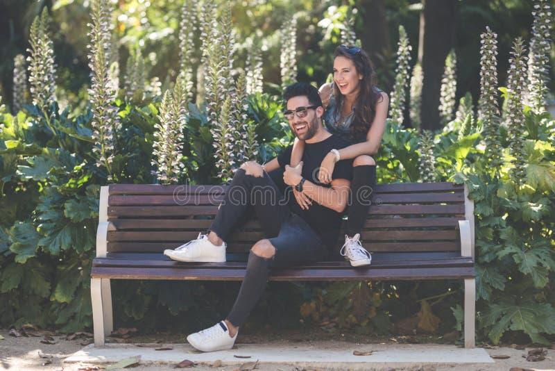 Couples riants se reposant ensemble sur le banc photographie stock libre de droits