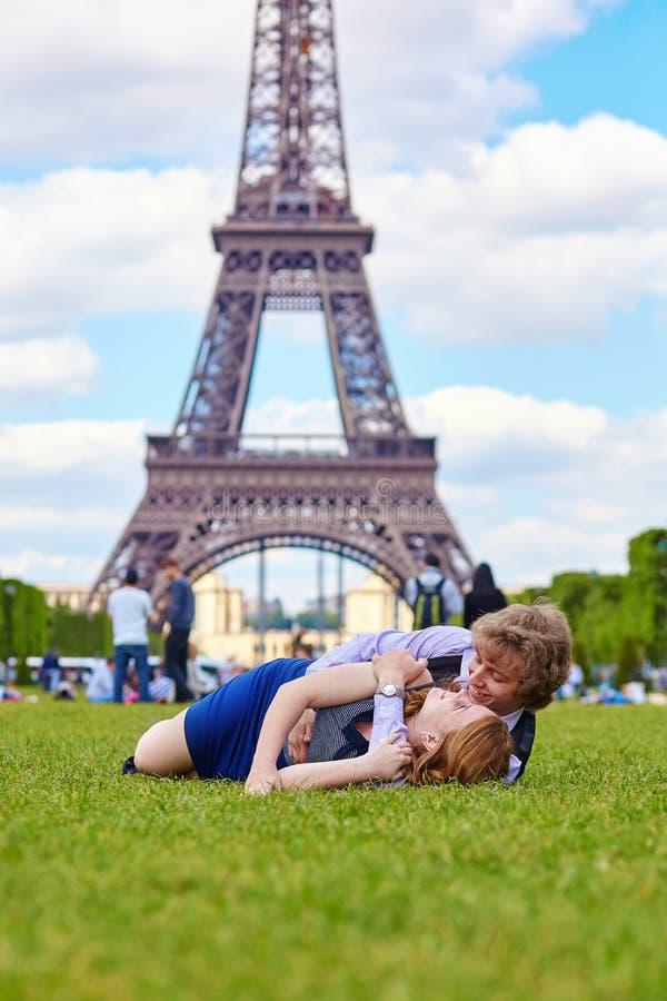 Couples riants se trouvant sur l'herbe à Paris photos libres de droits