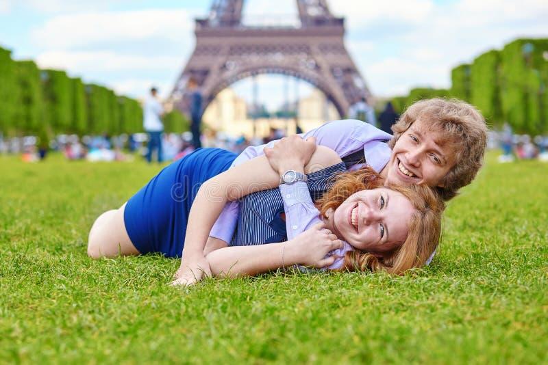 Couples riants se trouvant sur l'herbe à Paris photographie stock libre de droits
