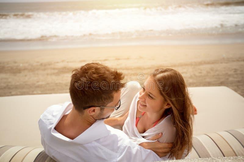 Couples riants se trouvant sur le lit pliant photographie stock libre de droits