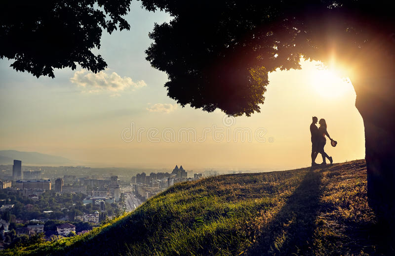 Couples romantiques à la vue de ville de coucher du soleil photographie stock libre de droits