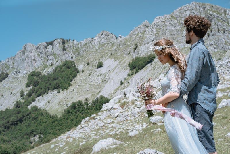 Couples romantiques élégants dans la perspective des montagnes images stock