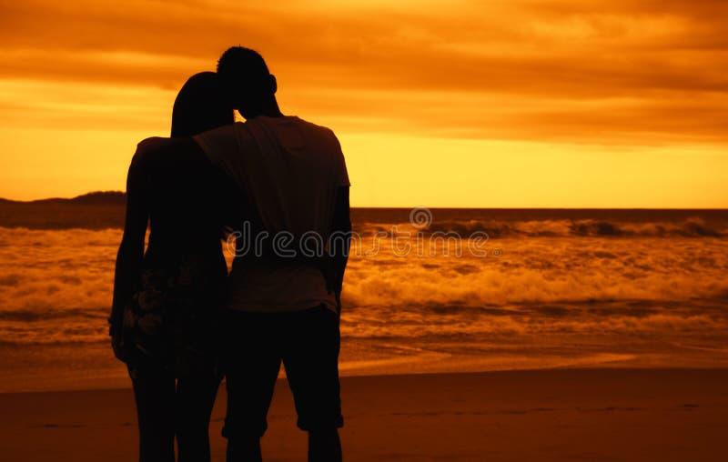 Couples romantiques dans des bras sur la plage au coucher du soleil photos stock