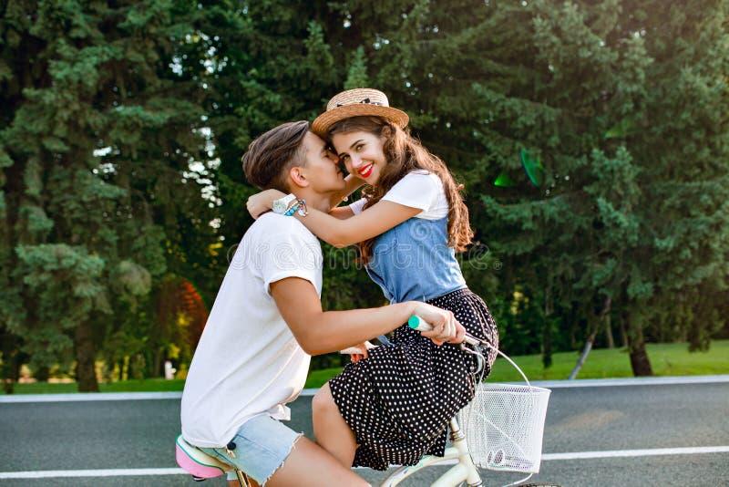 Couples romantiques dans l'amour sur le vélo sur le fond de forêt Type beau dans le T-shirt blanc conduisant le vélo, fille avec  photo stock