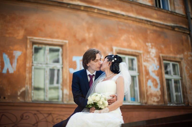 Couples romantiques de la séance de jeunes mariés et pose et le kissin images stock