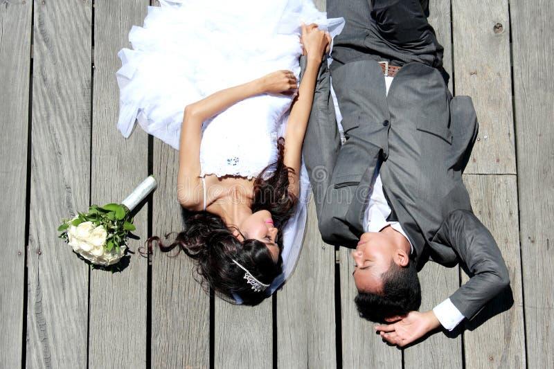 Couples romantiques de nouveaux mariés se couchant ensemble dans le jour ensoleillé image stock