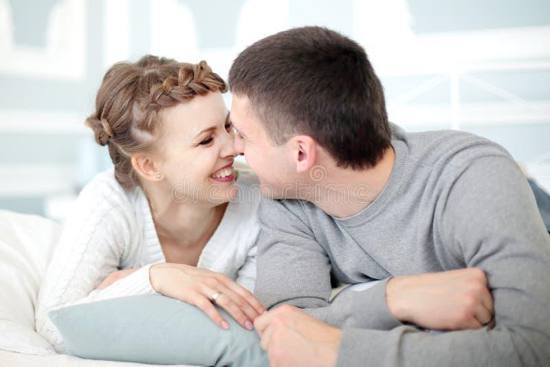 Couples romantiques de sourire de jeunes d?tendant dans chaque autres la soci?t? images stock