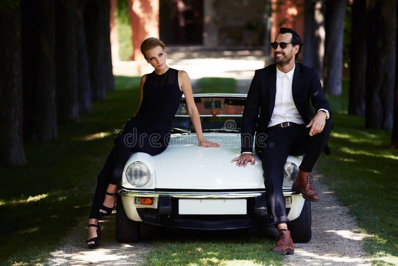 Couples romantiques et à la mode posant sur la voiture de luxe de cabriolet dehors en été photos stock