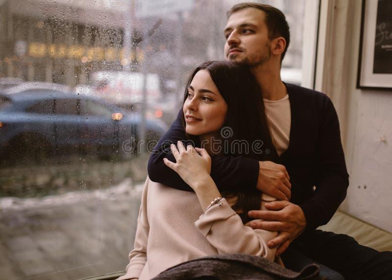 Couples romantiques Le type aimant ?treint sa belle amie s'asseyant sur le rebord de fen?tre dans un caf? confortable image stock