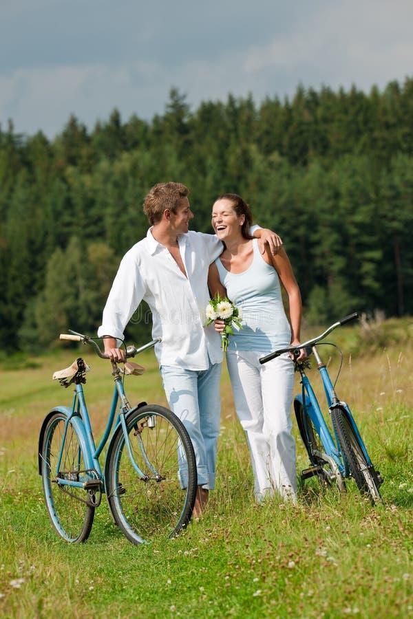 Couples romantiques marchant avec le vieux vélo dans le pré photographie stock libre de droits