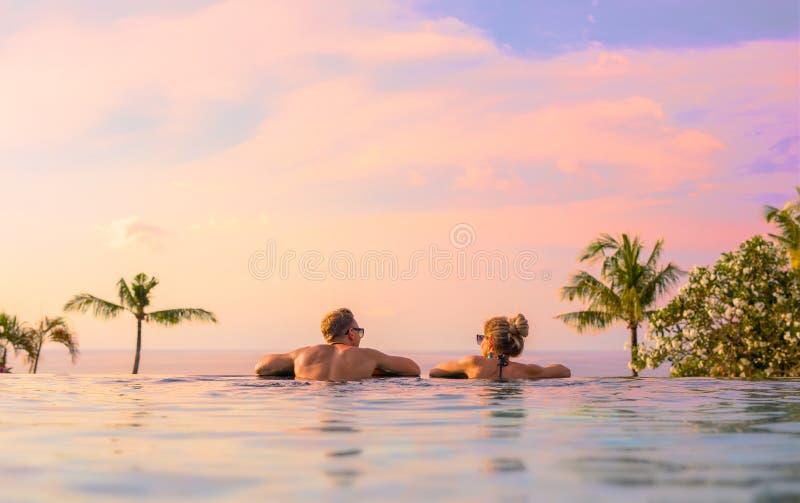 Couples romantiques regardant le beau coucher du soleil dans la piscine de luxe d'infini photos libres de droits