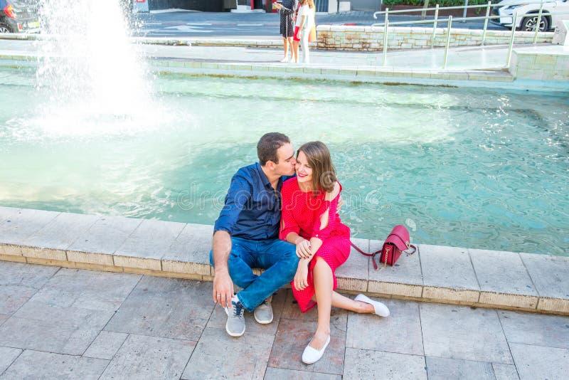 Couples romantiques se reposant sur le banc près de la fontaine de ville et appréciant des moments de bonheur Amour, datation, ro images stock