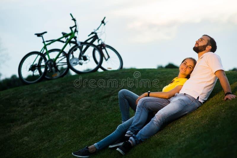 Couples romantiques se reposant sur le pré vert au coucher du soleil image libre de droits