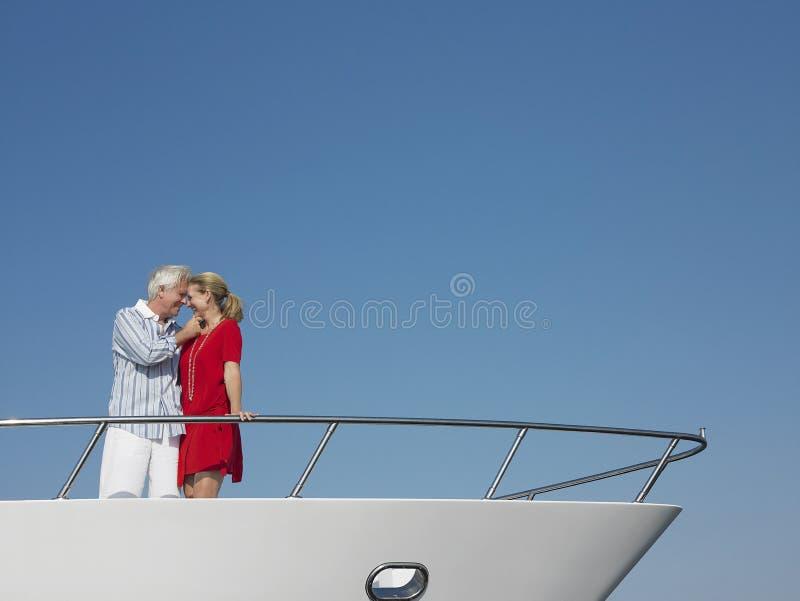 Couples romantiques se tenant sur l'arc du yacht photos libres de droits