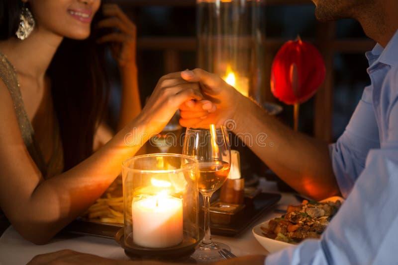 Couples romantiques tenant des mains ensemble au-dessus de la lueur d'une bougie images stock