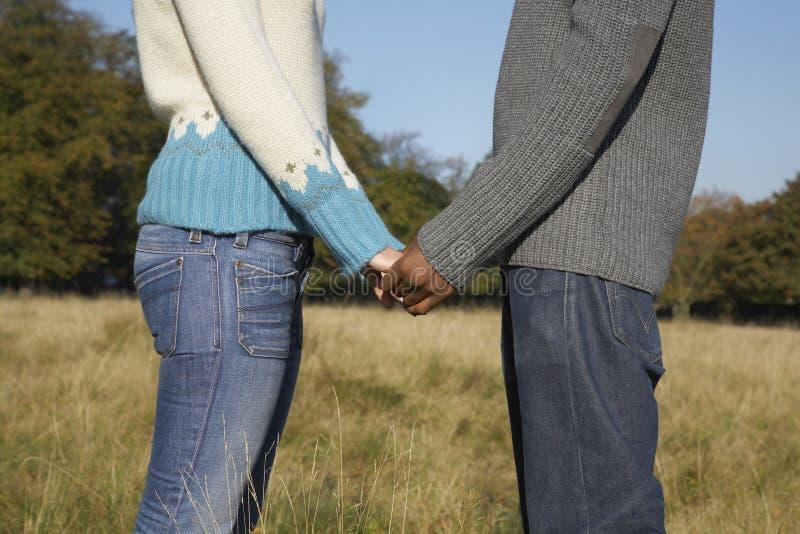Couples romantiques tenant des mains tout en tenant le champ de N image stock