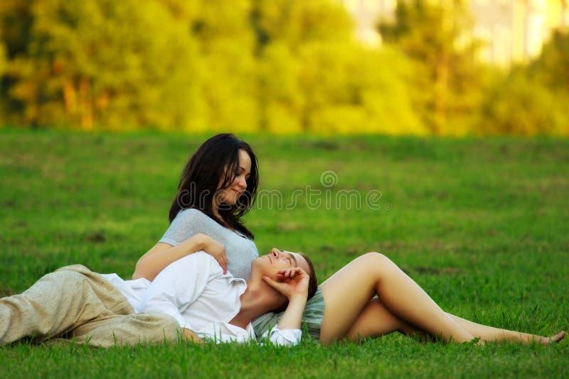 Couples s'étendant sur la pelouse de stationnement photo stock