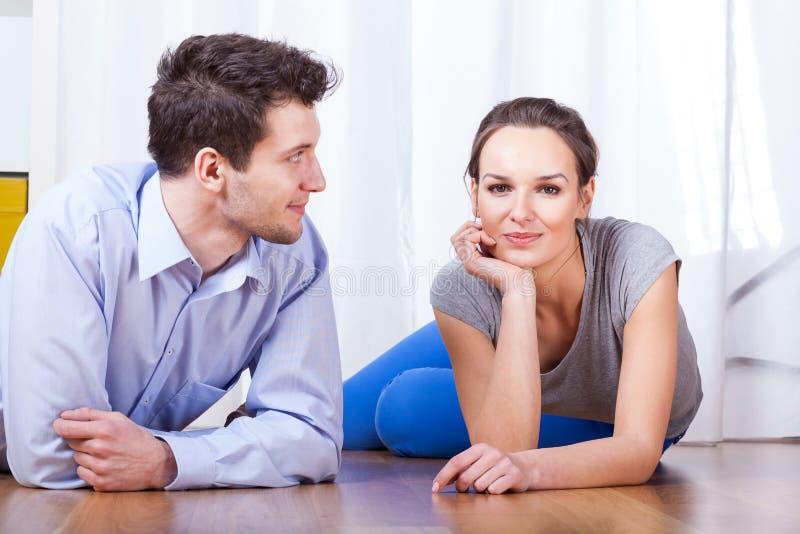 Couples s'étendant sur le plancher images stock