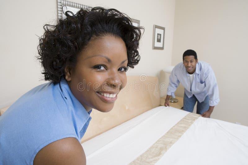 Couples s'chargeant du lit à la maison images libres de droits