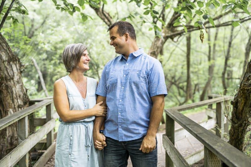 Couples s'embrassant ayant la promenade dans la forêt d'été images libres de droits