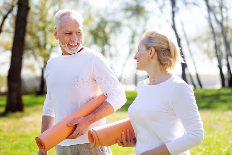 Couples sains actifs tenant des tapis de yoga images stock