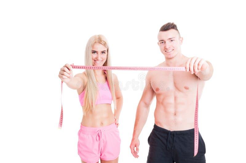 Couples sains de forme physique tenant le mètre ou le centimètre photos libres de droits