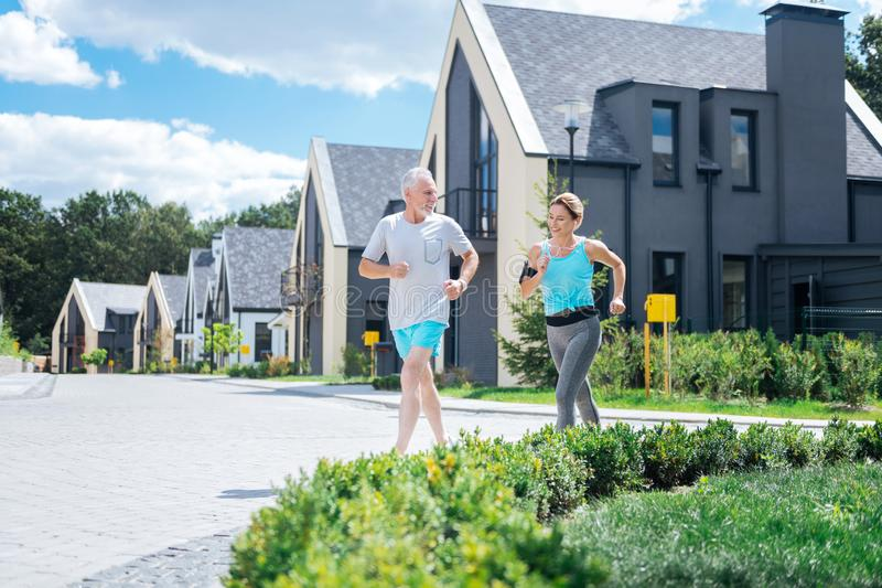 Couples sains des hommes d'affaires courant près de leur maison pendant le matin ensemble photo libre de droits