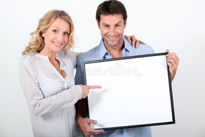 Couples se dirigeant au panneau blanc photographie stock