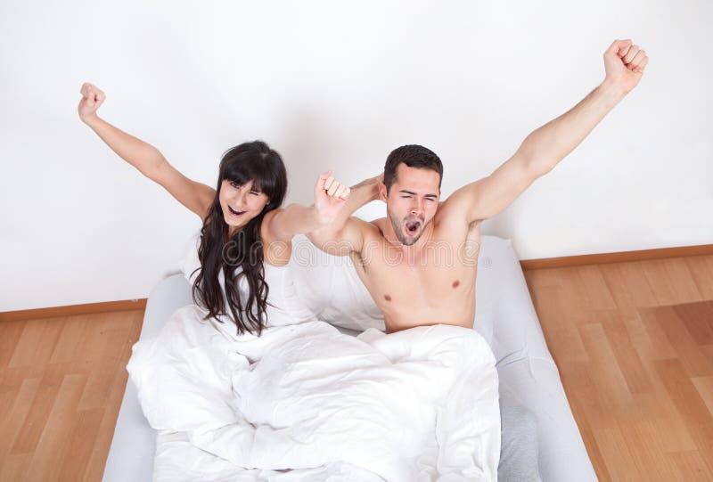 Couples se réveillant dans le bâti image stock