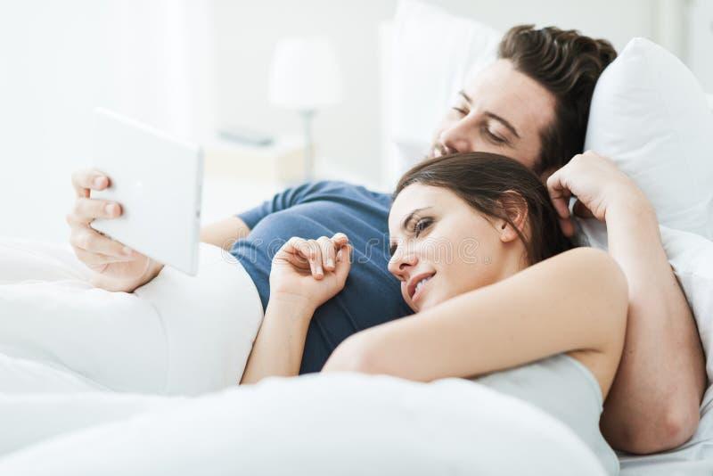 Couples se reliant à un comprimé images stock