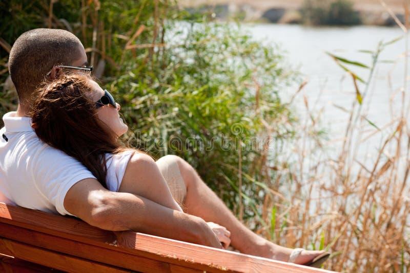 Couples se reposant au banc en bois photographie stock