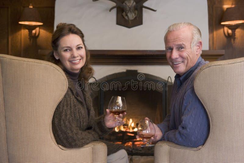 Couples se reposant dans la salle de séjour par la cheminée photographie stock libre de droits