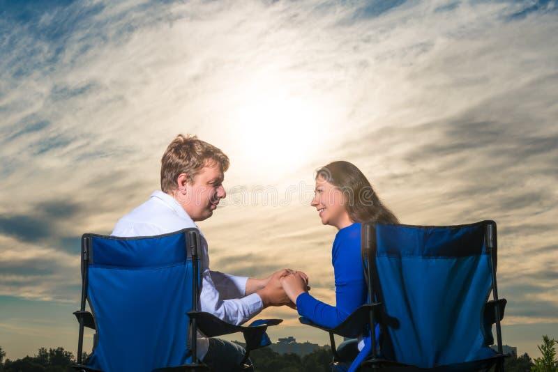Couples se reposant dans les chaises à l'aube photographie stock