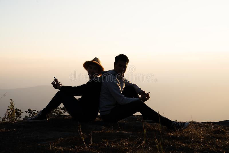 Couples se reposant de nouveau au dos utilisant les téléphones intelligents dans naturel image stock
