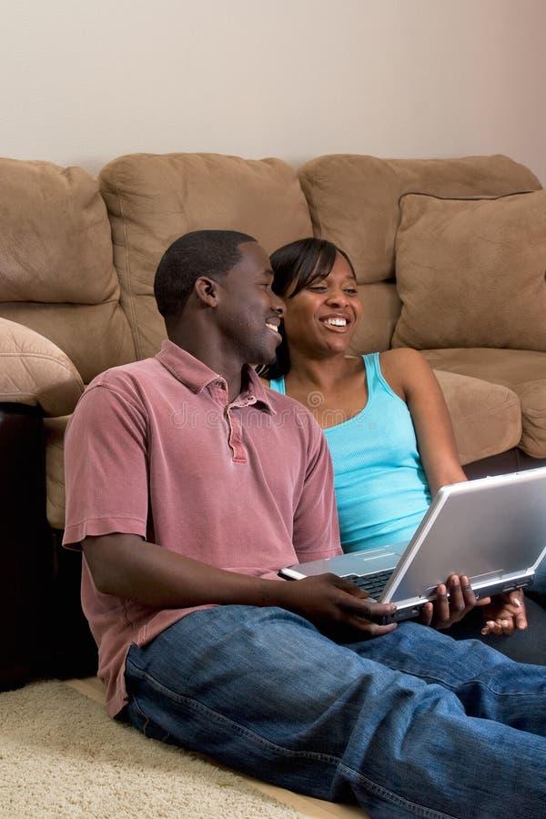 Couples se reposant devant le divan avec COM d'ordinateur portatif images stock