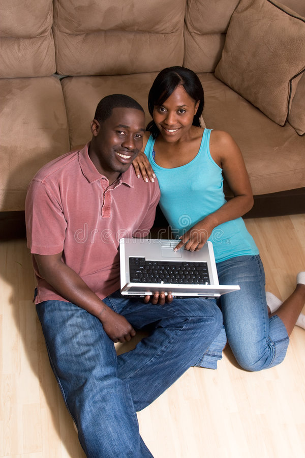 Couples se reposant devant le divan avec COM d'ordinateur portatif photos stock