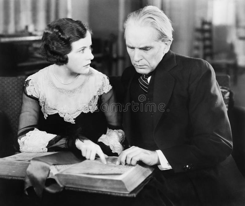 Couples se reposant ensemble et regardant un livre avec une expression du visage inquiétée (toutes les personnes représentées ne  image stock