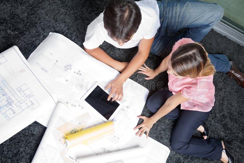 Couples se reposant sur la couverture avec des plans de Chambre photo libre de droits
