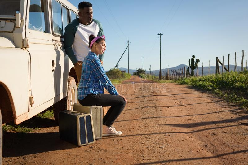 Couples se reposant sur la valise à la campagne images stock