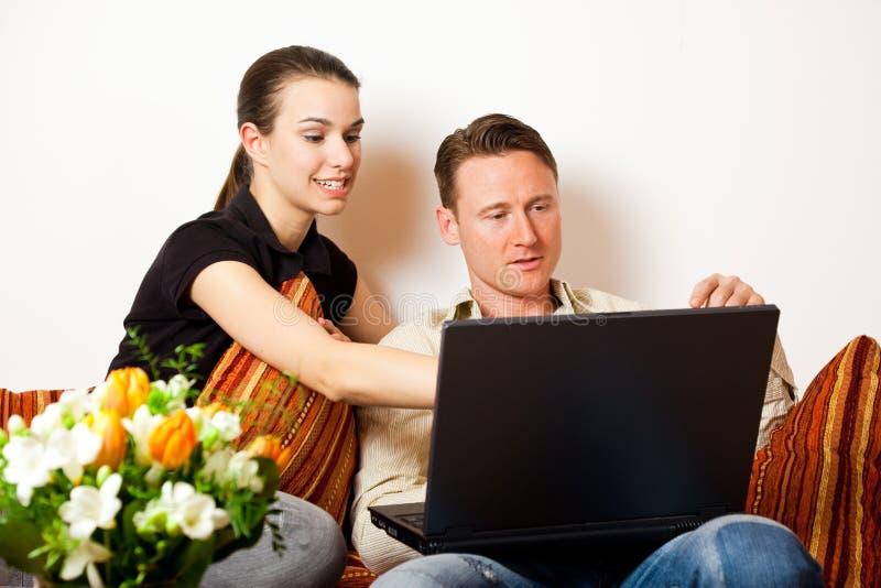 Couples se reposant sur le divan avec un ordinateur portable photo libre de droits