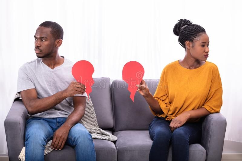 Couples se reposant sur Sofa Holding Broken Heart photo libre de droits